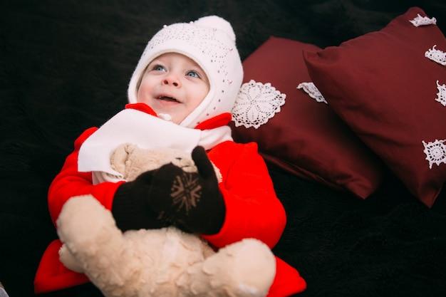 Menina feliz no casaco vermelho com ursinho de pelúcia deitado sobre uma manta e desfrutando de um belo dia de inverno na floresta