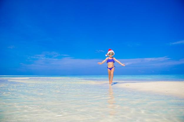 Menina feliz no chapéu de papai noel na praia durante as férias