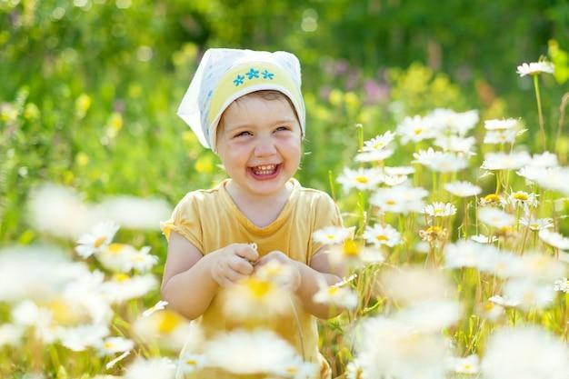 Menina feliz no prado da margarida
