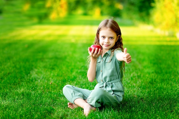 Menina feliz no verão no gramado com uma maçã vermelha na grama verde e mostra a classe, espaço para texto