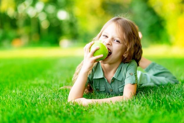 Menina feliz no verão no gramado morde uma maçã verde com dentes saudáveis na grama e sorri, espaço para texto