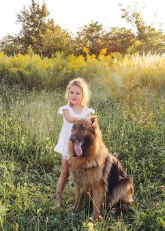 Menina feliz no vestido branco acariciando o cachorro grande em pé na grama verde na primavera. pastor alemão