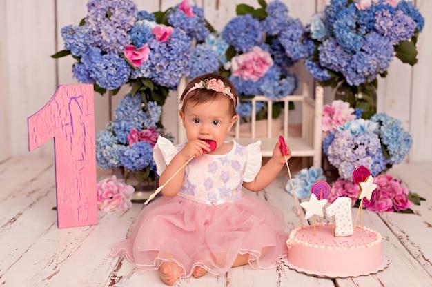 Menina feliz no vestido comendo bolo de aniversário
