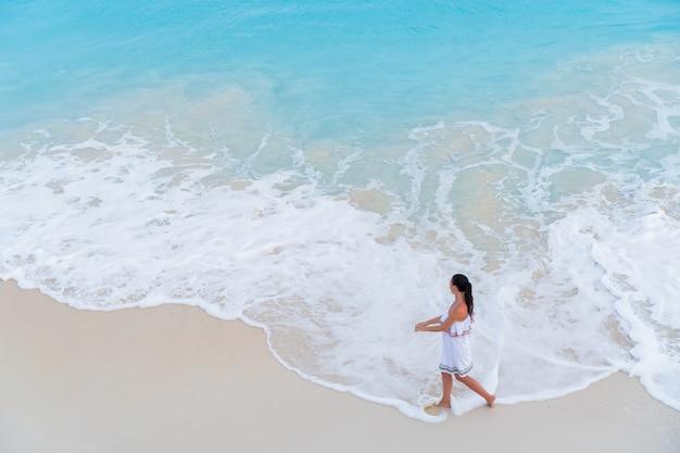 Menina feliz nova do turista na praia na água pouco profunda. vista superior de uma moça e de uma praia neve-branca com agua potável de turquesa.