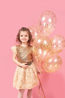 Menina feliz num vestido brilhante segurando balões