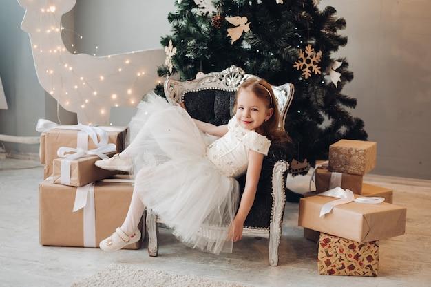 Menina feliz num vestido relaxante na poltrona por árvore de natal.