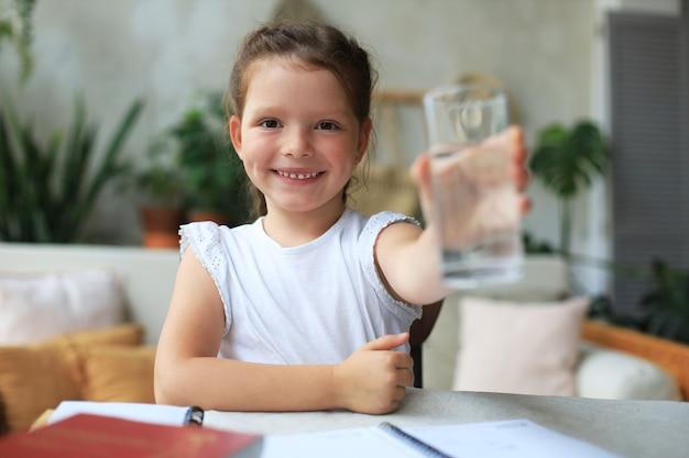Menina feliz oferece água mineral cristalina de vidro, criança pequena recomenda uma dose diária de água limpa.