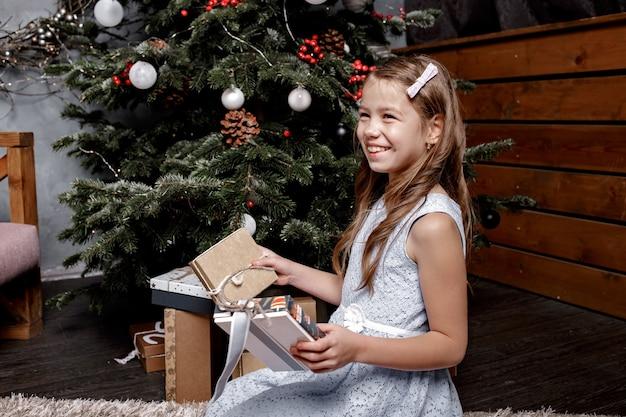 Menina feliz olha para os presentes de natal perto da árvore de natal atrás.