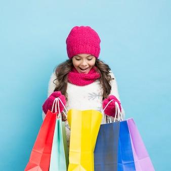 Menina feliz olhando em sacolas de compras