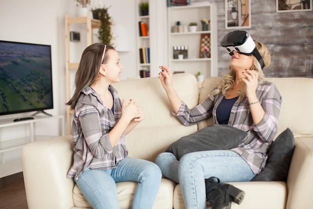 Menina feliz olhando para a mãe dela enquanto usa o fone de ouvido da realidade virtual. paternidade moderna.