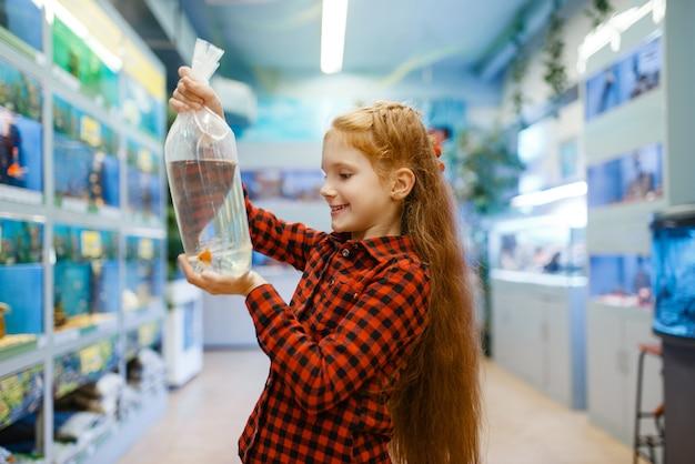 Menina feliz olhando peixinho na loja de animais. criança comprando equipamentos em petshop, acessórios para animais domésticos