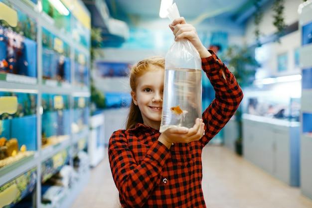 Menina feliz olhando peixinho na loja de animais. criança comprando equipamentos em petshop