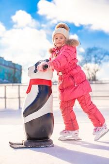 Menina feliz patinando na pista de gelo