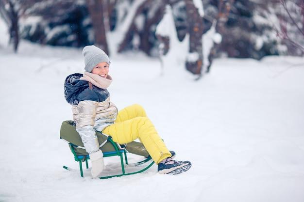 Menina feliz pequena adorável que sledding no dia nevado do inverno.