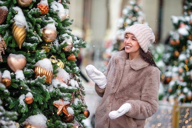 Menina feliz perto da filial do abeto na neve por o ano novo.