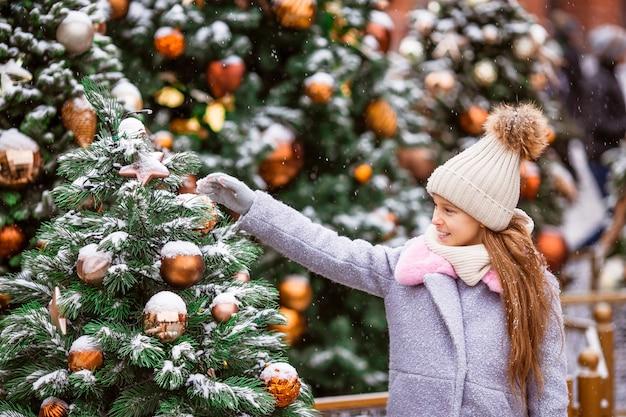 Menina feliz perto de galho de abeto na neve pelo ano novo.