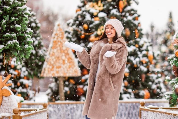 Menina feliz perto do ramo de abeto na neve pelo ano novo.