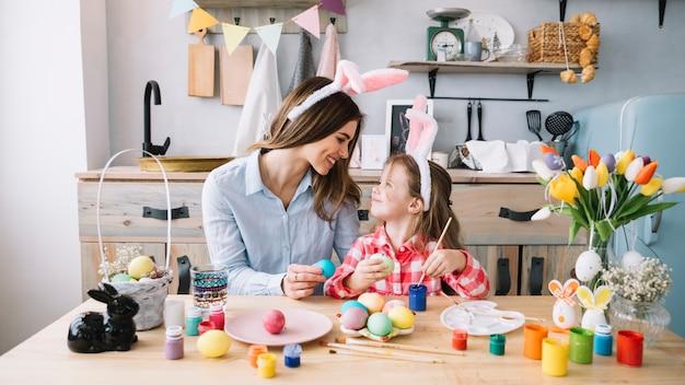 Menina feliz pintando ovos para a páscoa com a mãe