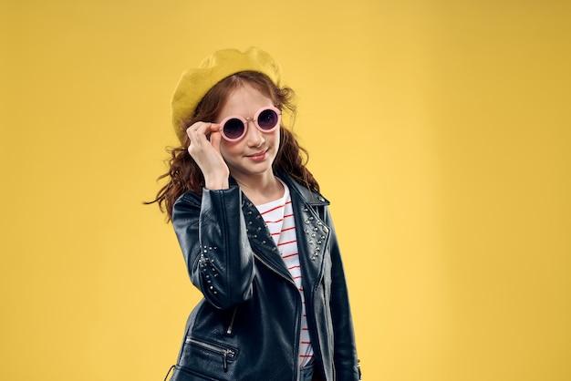 Menina feliz posando em uma parede amarela