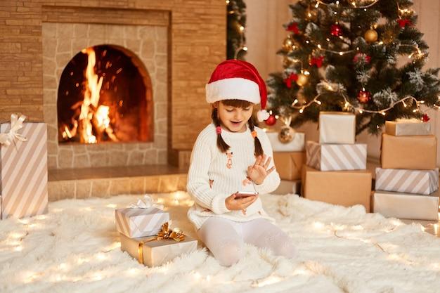Menina feliz positiva vestindo suéter branco e chapéu de papai noel, sentado no chão perto da árvore de natal, caixas de presentes e lareira, tendo videochamada com amigos via smartphone.