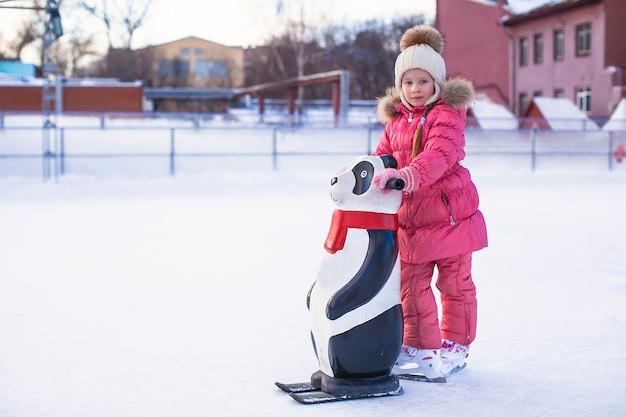 Menina feliz que aprende a patinar na pista