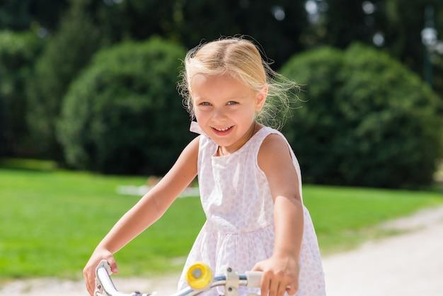 Menina feliz que biking aprendendo como usar uma bicicleta em um parque