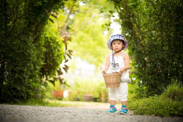Menina feliz que corre com cesta a exploração agrícola do jardim.