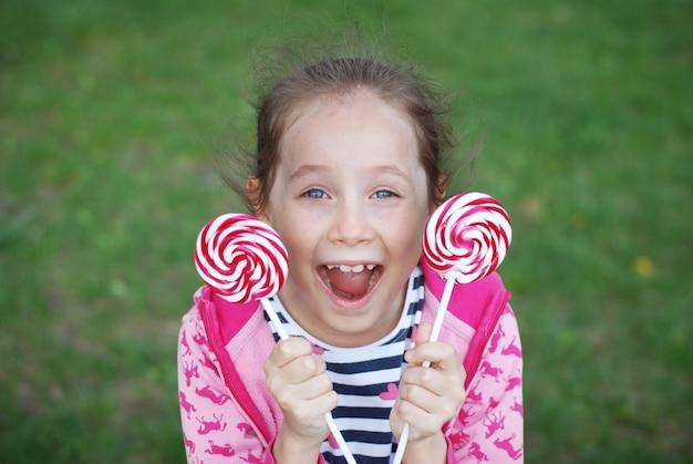 Menina feliz que guarda doces do redemoinho do pirulito. verão, se divertindo.