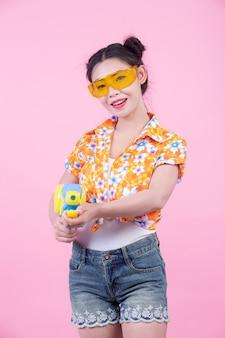 Menina feliz que guarda uma arma de água cor-de-rosa do fundo.