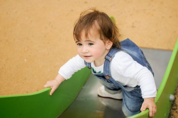 Menina feliz que joga em um campo de jogos urbano.