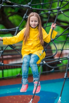Menina feliz que joga no campo de jogos ao ar livre no dia do outono