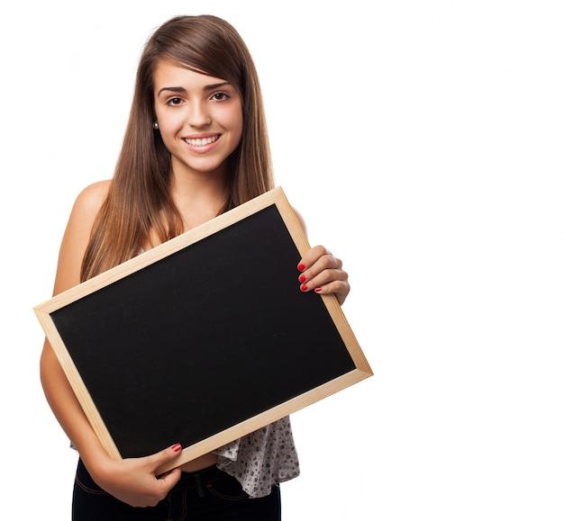 Menina feliz que mostra um pequeno quadro-negro