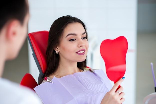 Menina feliz que olha no espelho em um sorriso na odontologia.