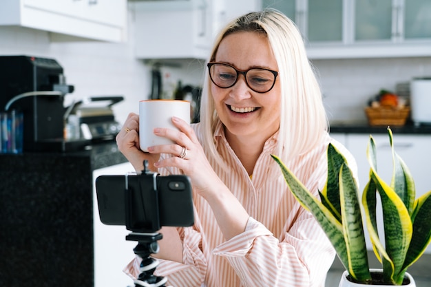Menina feliz que senta em casa a cozinha e que guarda o videocall. jovem mulher usando smartphone para vídeo chamada com amigo ou família. webinar de gravação do vlogger. mulher olhando a câmera e acenando as mãos de saudação