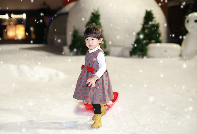 Menina feliz que veste um vermelho - o revestimento cinzento tem um divertimento na neve, tempo de inverno.
