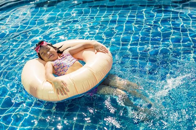 Menina feliz relaxante com anel inflável colorido na piscina ao ar livre em dia quente de verão
