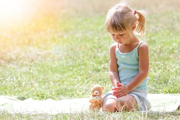 Menina feliz rezando na natureza no parque natural
