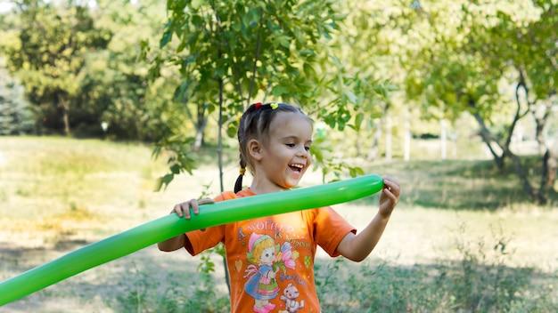 Menina feliz rindo brincando com um balão de festa verde longo e fino ao ar livre no parque