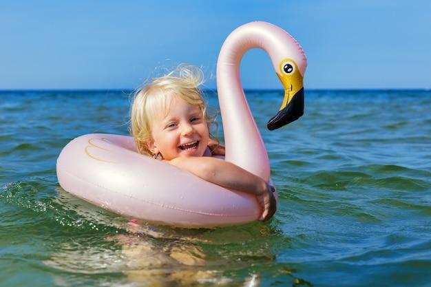 Menina feliz rindo e nadando no mar com o flamingo de anel de borracha
