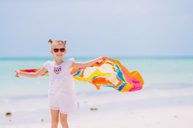 Menina feliz se divertindo correndo com pareo na praia tropical branca