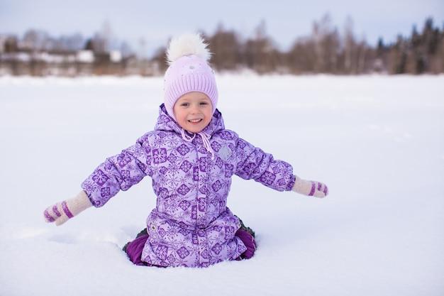 Menina feliz se divertindo na neve no dia ensolarado de inverno