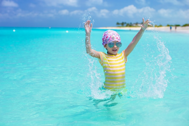 Menina feliz se divertir na praia durante férias nas caraíbas