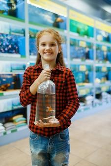 Menina feliz segura peixinho dourado e faz um pedido, loja de animais. criança comprando equipamentos em petshop, acessórios para animais domésticos