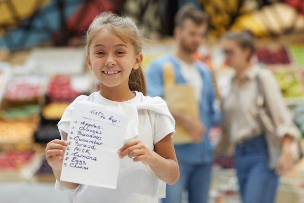 Menina feliz, segurando a lista de compras