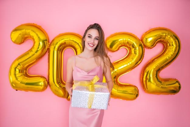 Menina feliz segurando caixa de presente isolada na celebração de ano novo de balões de ar de fundo rosa