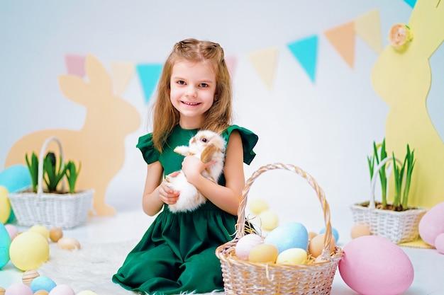 Menina feliz, segurando o coelhinho fofo perto de ovos de páscoa pintados