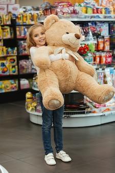 Menina feliz, segurando o grande urso de pelúcia