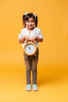 Menina feliz segurando o relógio despertador.