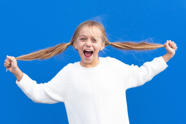 Menina feliz segurando rabo-de-cavalo e rindo