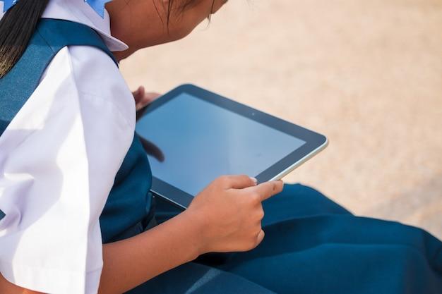 Menina feliz segurando tablet pc ao ar livre no parque de verão